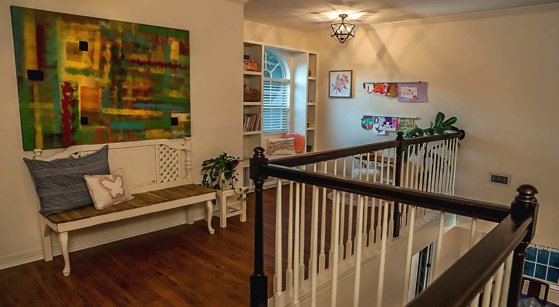 Landing, photographed after makeover, with vinyl plank flooring, art hanging on the walls, a windowseat bookcase and a bench
