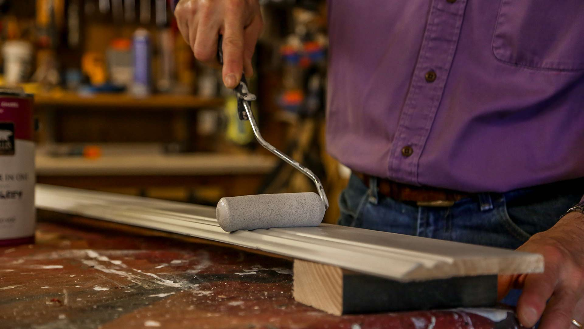 Painting wooden baseboard with a foam trim roller in a workshop.