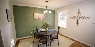 Dining room with green accent wall and chandelier above the table