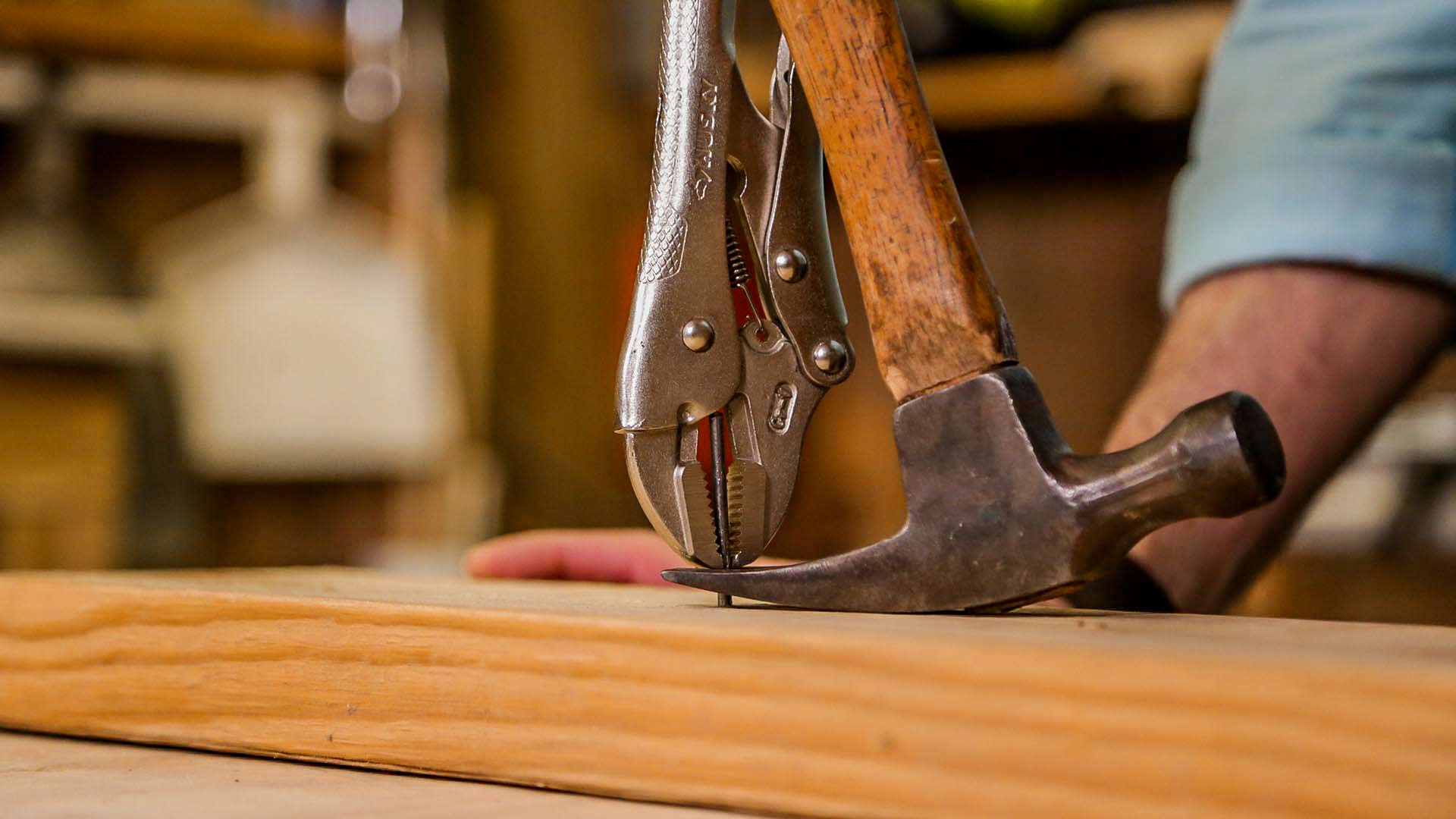 Joe Truini removes a nail from lumber with a hammer and a pair of locking pliers