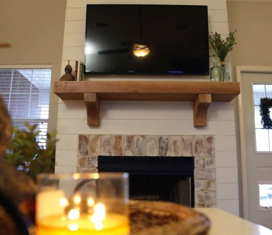 Faux shiplap fireplace with mantel and candle on accent table