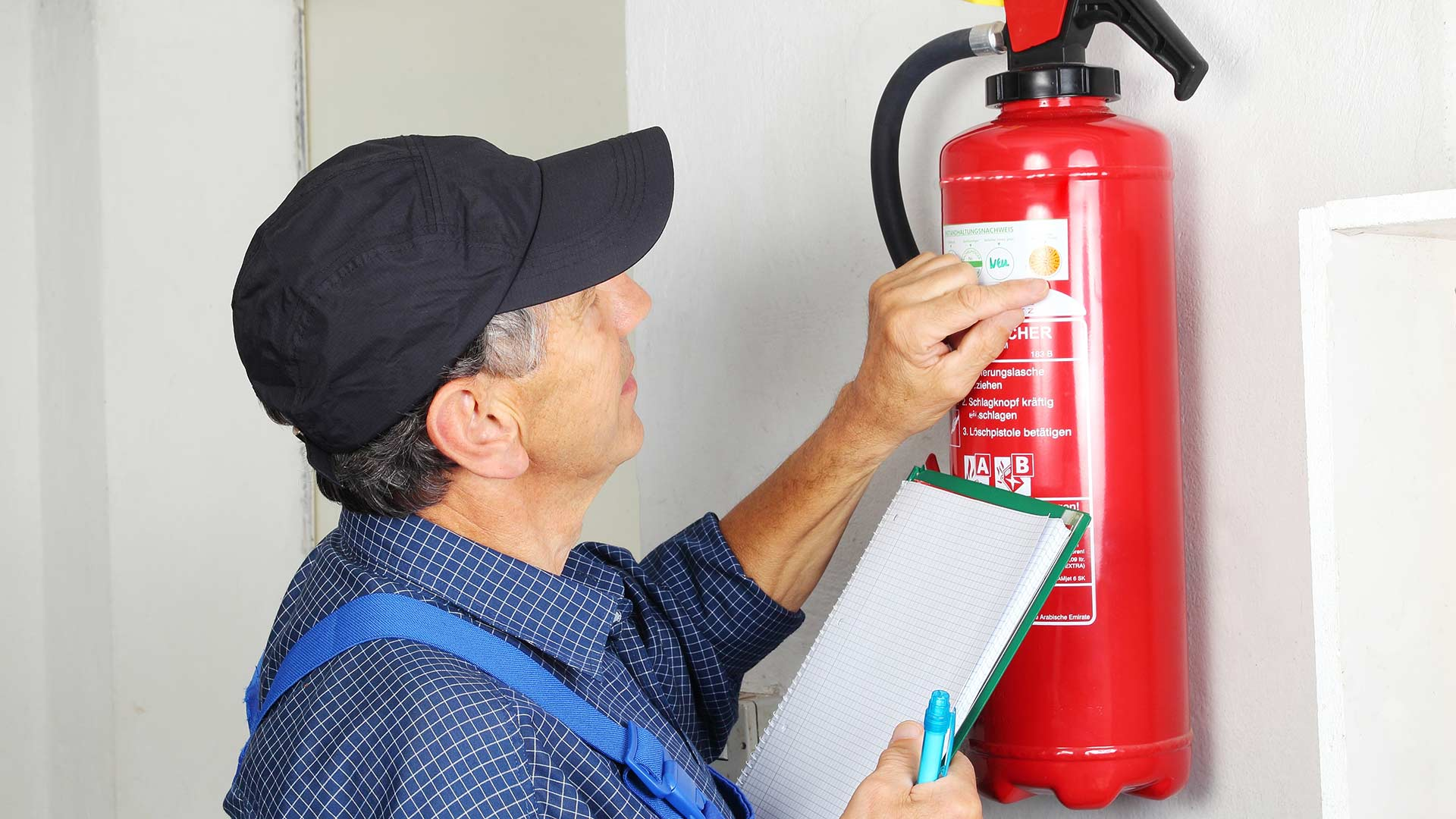 Man services a fire extinguisher that's hanging on the wall