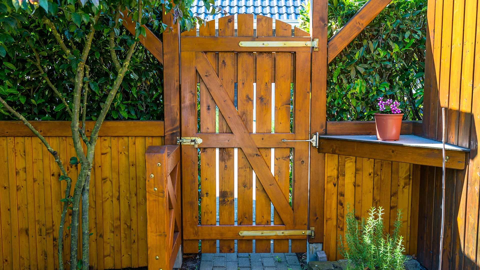 Tall wooden fence gate leading to a beautifully landscaped patio