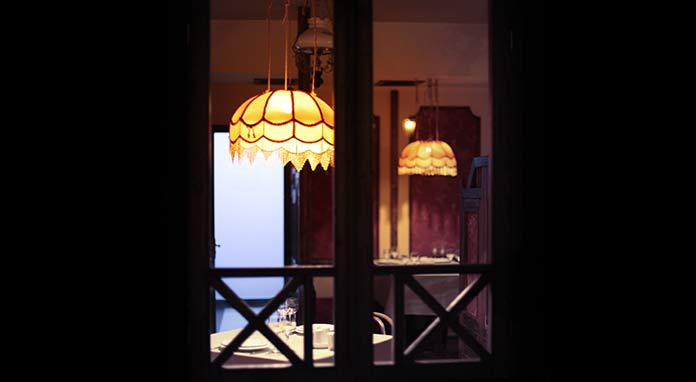 Windows open at night, allowing the glow of pendant lights to be seen from outside