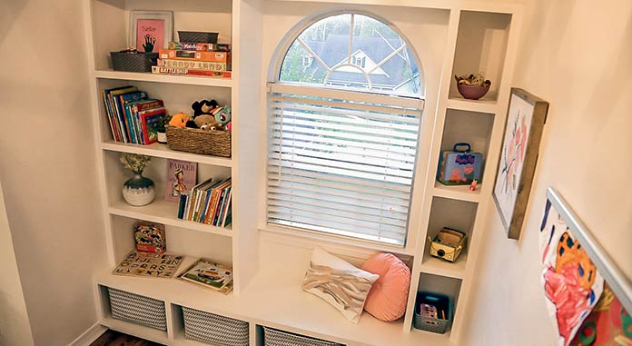 Windowseat bookcase built around an arched window. The bookcase is filled with toys and books.