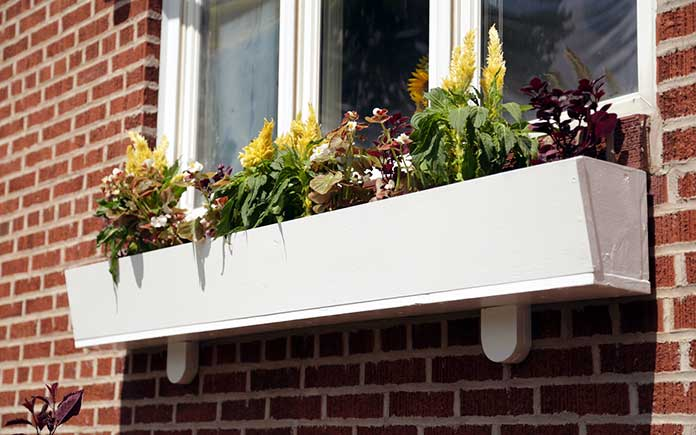 A homemade wooden window box installed under a window on a brick home