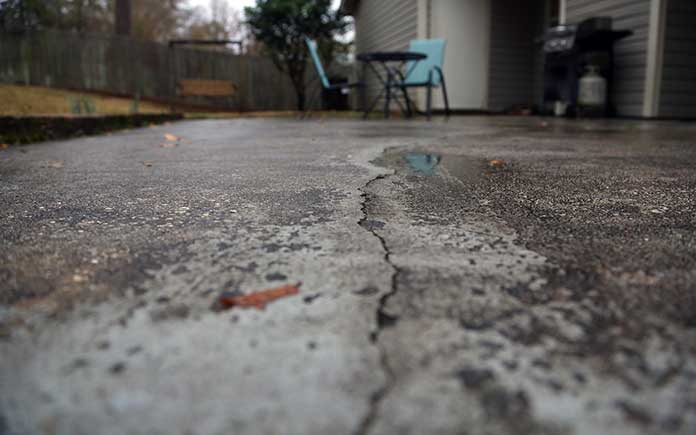 A worn-out concrete patio with hairline cracks and discoloration