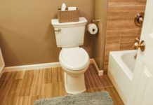 Bathroom with luxury vinyl flooring, a toilet and brown-painted walls.