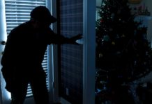 Burglar entering home with lights off and nearby Christmas tree