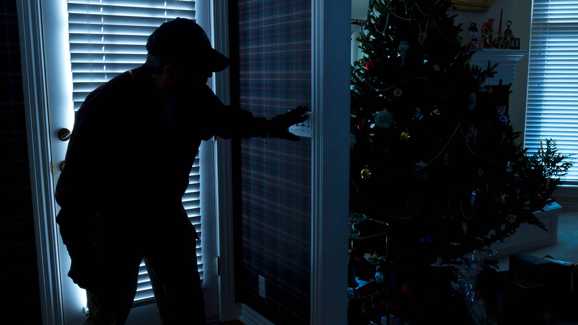 Burglar entering a dark home with the lights off and Christmas tree in view.