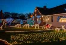 Christmas lights display on house lawn and roof
