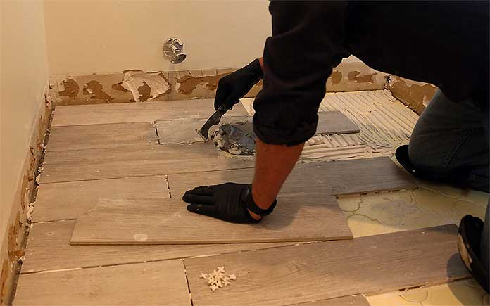 Danny Lipford laying ceramic tile floors in a bathroom