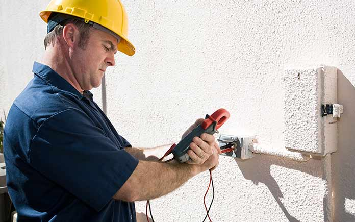 Electrician checking electrical box voltage