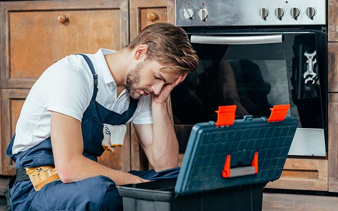 Frustrated man sitting on the kitchen floor beside broken an oven and a toolbox