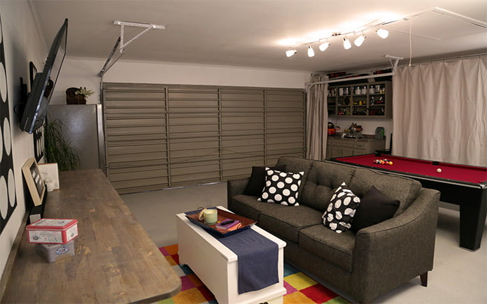 Garage transformed into multipurpose room with a couch and pool table