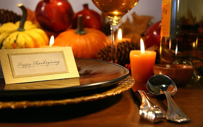 Thanksgiving place setting with charger plates, candles, silverware and pumpkins