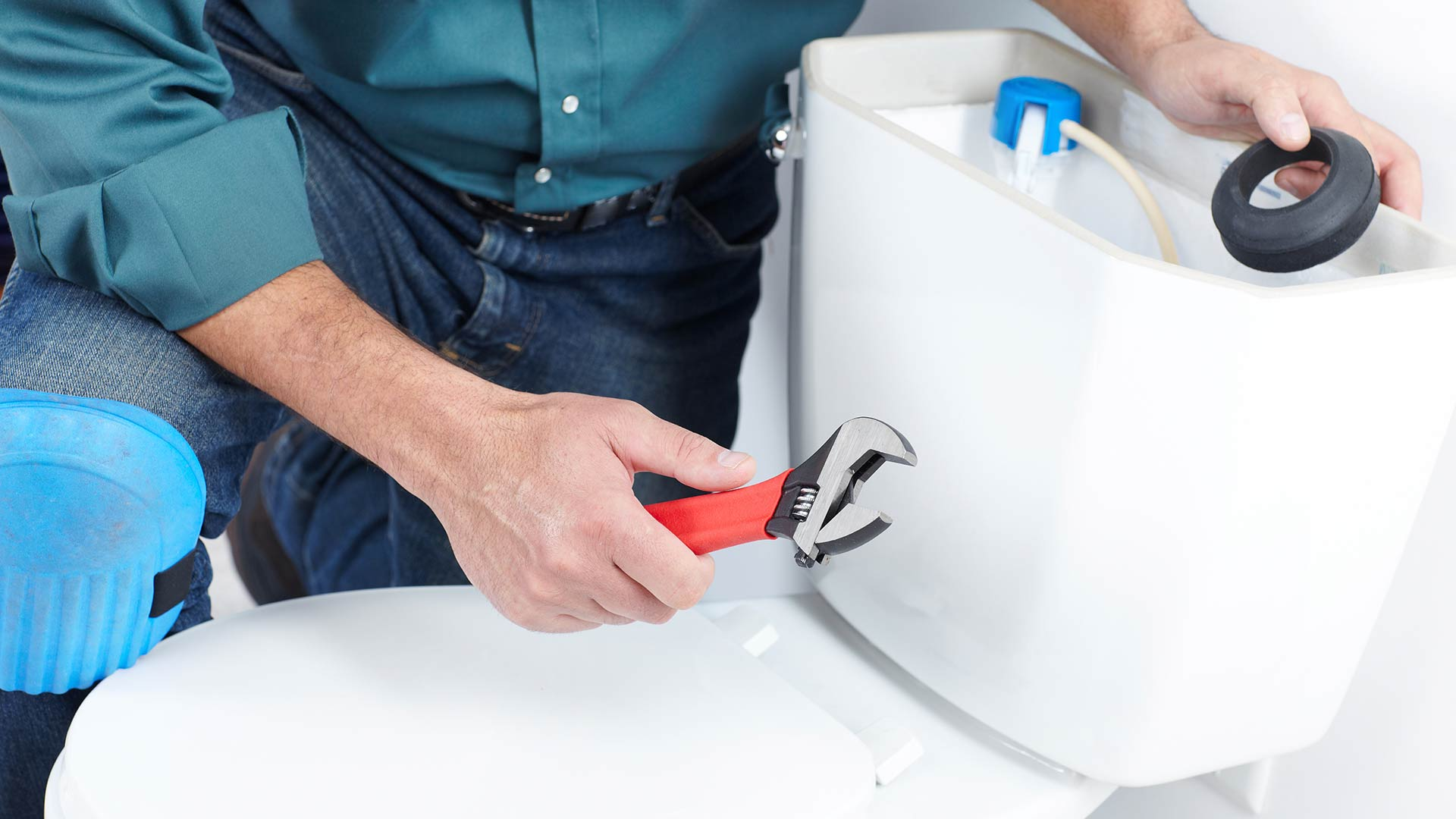 Man with a wrench and a wax seal installing a toilet