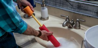 Joe Truini siphons standing water from a bathroom sink with a water toy
