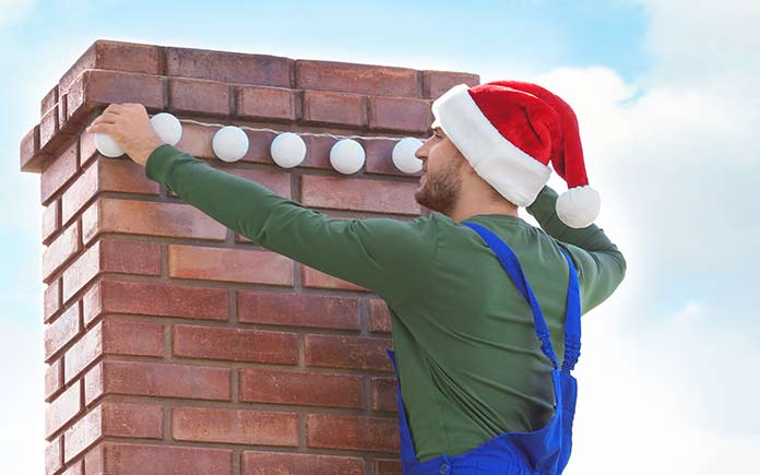 Man in Santa hat hanging Christmas lights around chimney