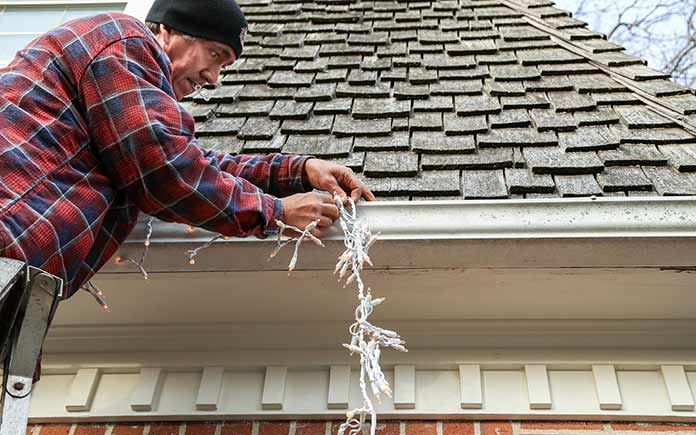 Man on a ladder hanging Christmas string lights