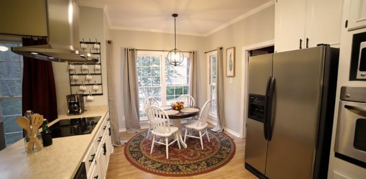 Modern kitchen makeover with white painted cabinets and new Kichler light fixture, after photo