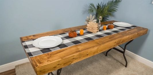 Thanksgiving buffet on plastic table topped with a homemade wood covering.