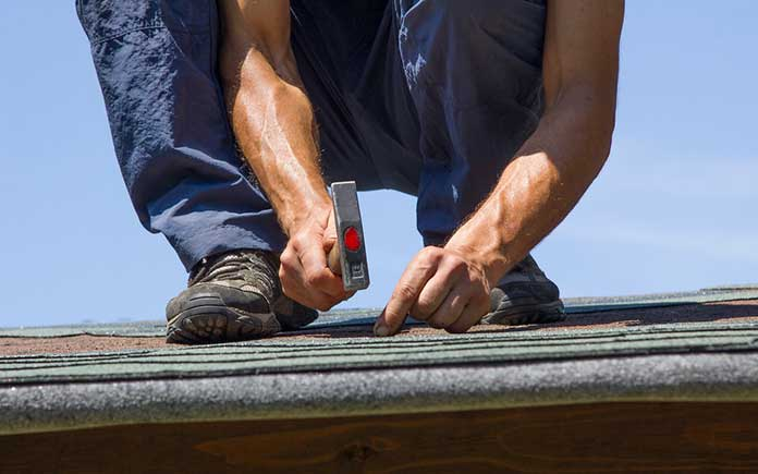 Man hammering a nail into an asphalt shingle on the roof