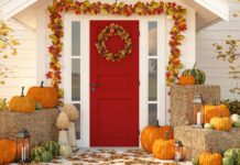Exterior Thanksgiving décor featuring fall garland, pumpkins, bales of hay and pumpkins