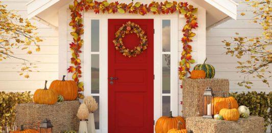 Exterior Thanksgiving décor featuring fall garland, pumpkins, bales of hay and pumpkins