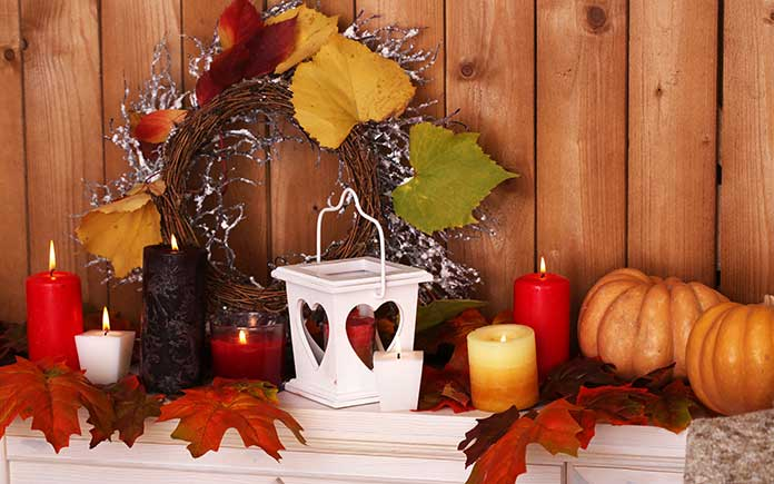 Thanksgiving décor on a mantel featuring pumpkins, candles and a wreath