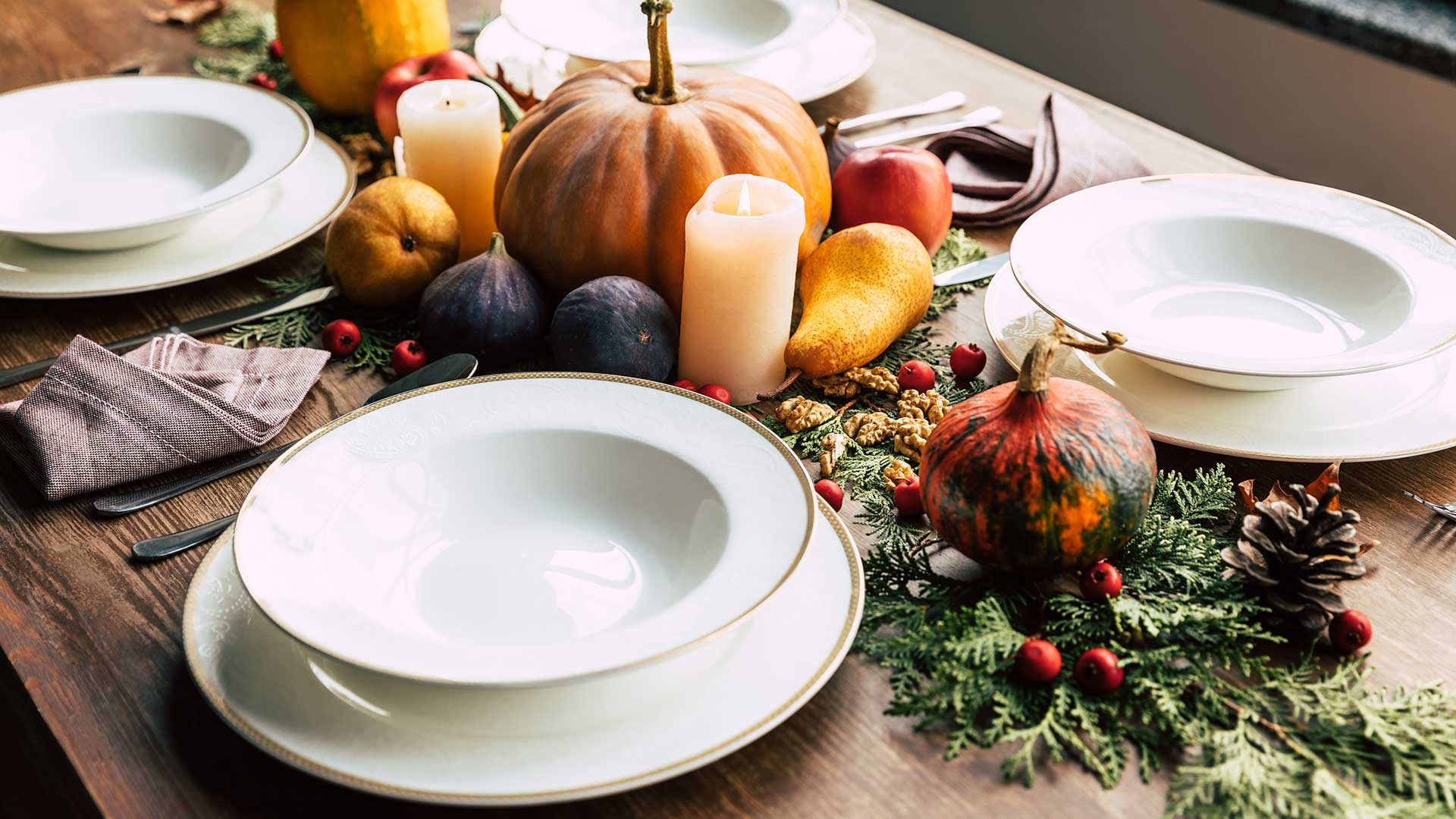 Thanksgiving table set with chargers, dinner plates and pumpkins