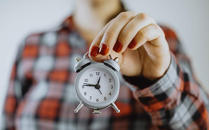 Woman holding alarm clock in hand