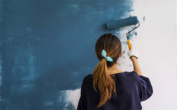 Young woman painting a blue wall