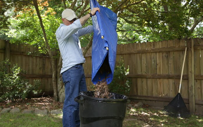 Joe Truini empties leaves out of a tarp into a trash can.