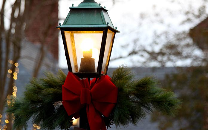 Red bow and garland around lamp post.