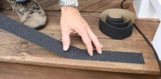Applying a self-adhesive strips to an exterior wood step.