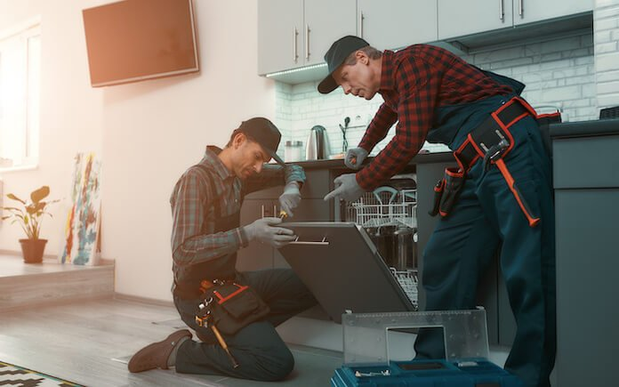 two repair men in kitchen
