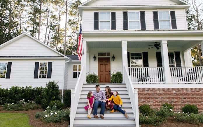 Family sitting on steps in front of house protected by a home warranty plan
