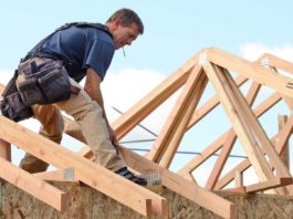 Home builder installing timber roof trusses