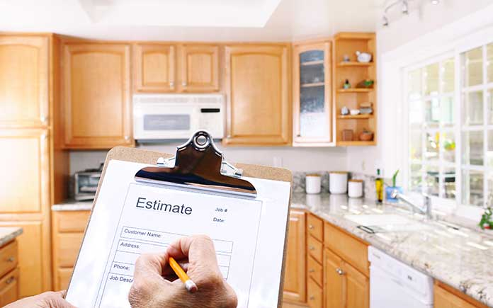 Homeowner holds clipboard and calculates estimate for kitchen remodeling