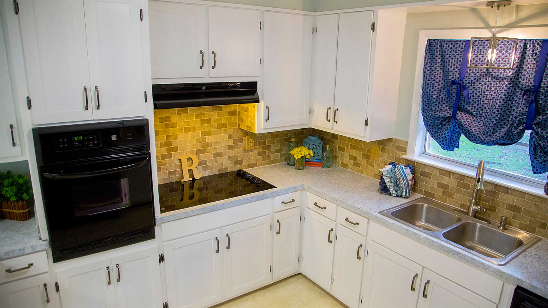 Kitchen with backsplash, white cabinets and freshly painted walls