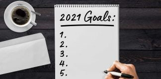 Note pad with a hand writing down 2021 goals