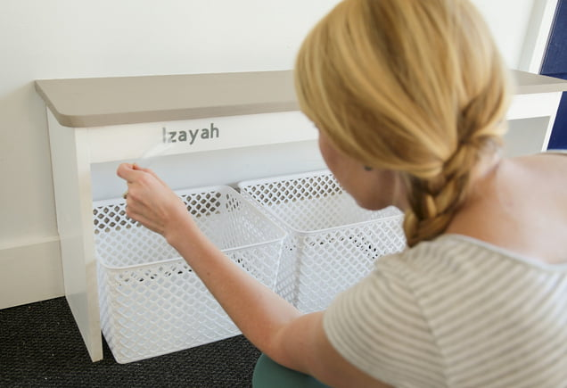 Chelsea Lipford Wolf adds labels to a drop zone storage bench.