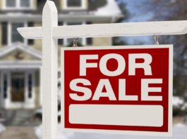 Winter real estate with for sale sign in front yard