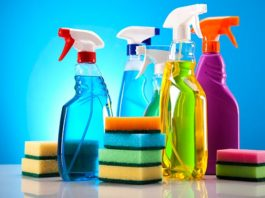 Assorted house cleaning products, spray bottles and sponges