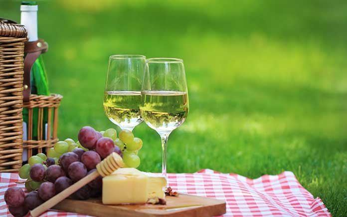 Wine and cheese tray arranged on a picnic tablecloth