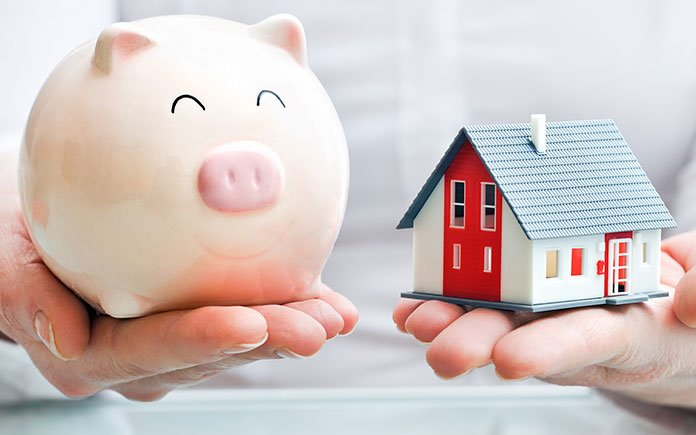 Piggy bank and house symbolizing real estate