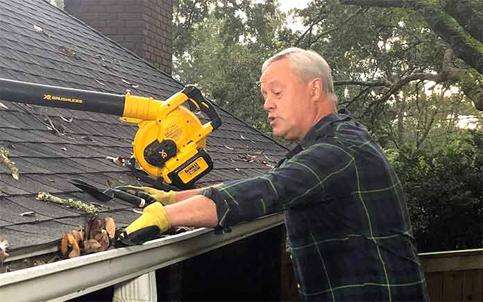 Danny Lipford removing leaves and other debris from a roof
