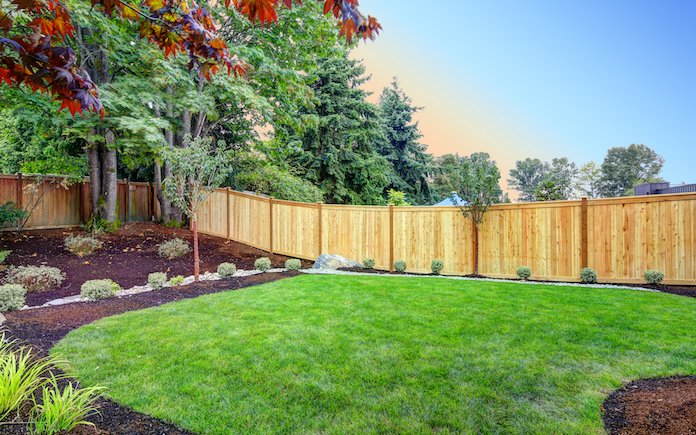 View of an attractive backyard with new planting beds and well kept lawn