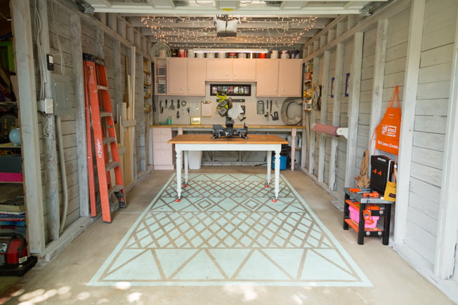 Chelsea Lipford Wolf's workshop, featuring a work table, painted concrete rug, pegboard and pink cabinets and a workbench.